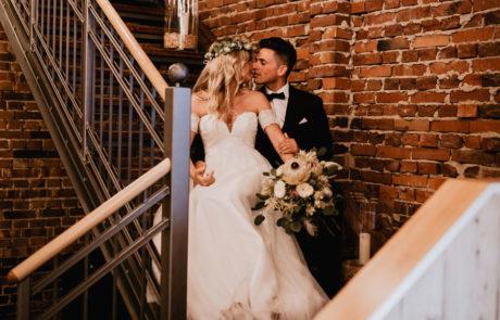 Brautpaar auf Treppe der Galerie Festscheune