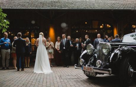 Brautpaar, Oldtimer und Gäste vor Hof Frien Festscheune